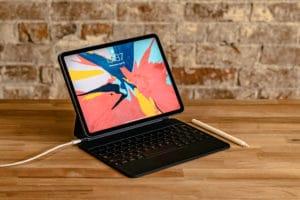 iPad Pro com Magic Keyboard e Apple Pencil sobre mesa de madeira