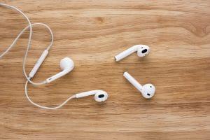 EarPods com fio numa mesa de madeira ao lado de AirPods