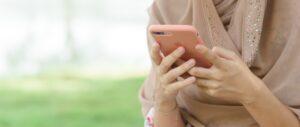 Mulher mexendo em iPhone rosa