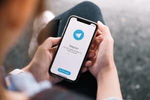 Homem usando Telegram em um iPhone