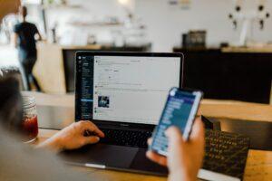 Pessoa usando iPhone e MacBook