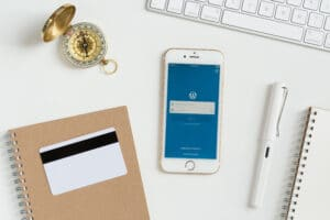 WordPress em iPhone sobre uma mesa cheia de objetos