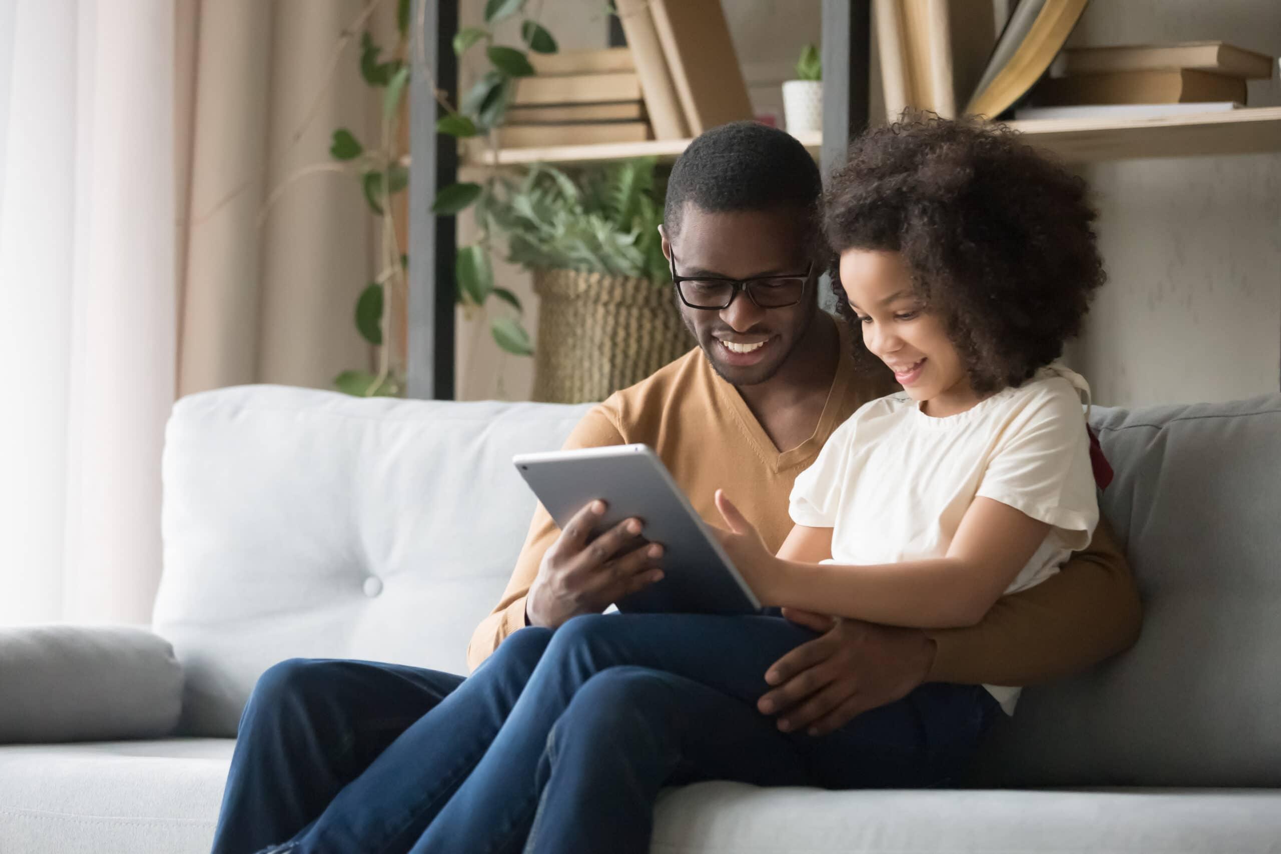 Pai e filha mexendo em iPad