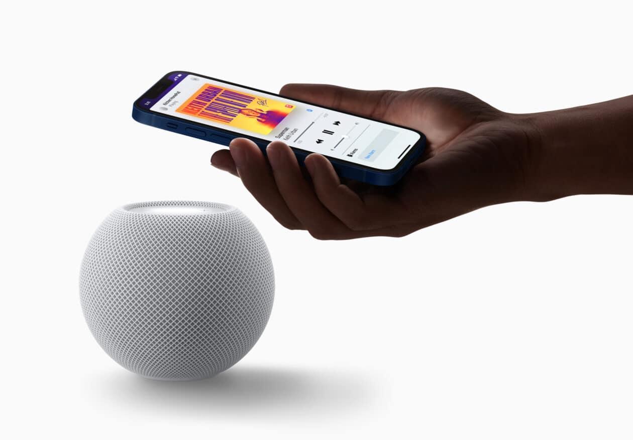 HomePod mini branco com mão segurando iPhone