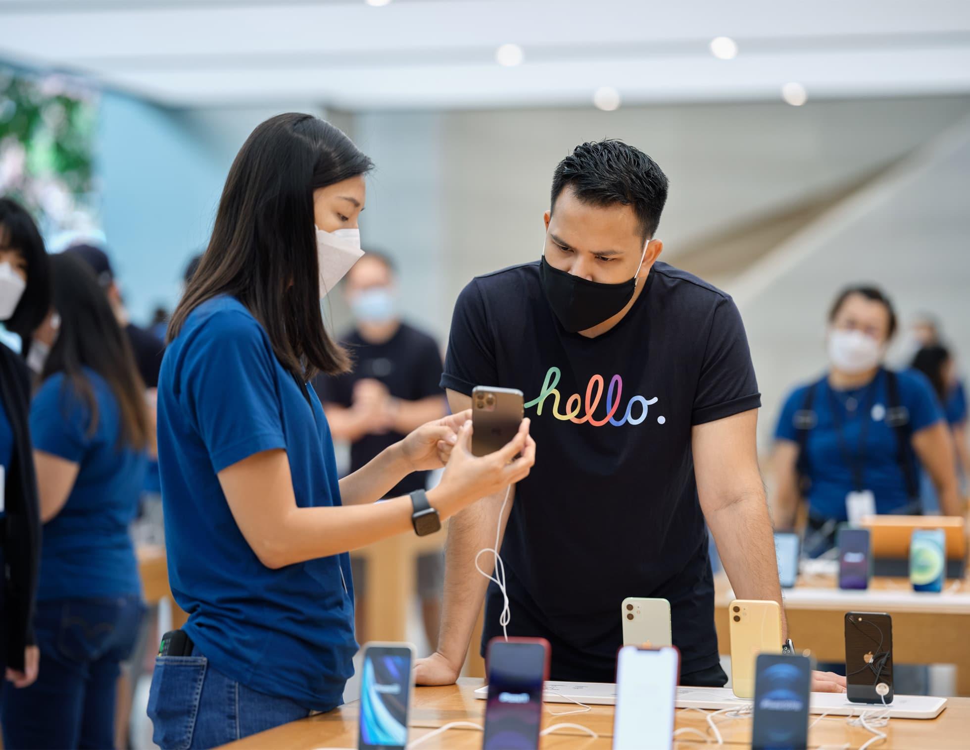 Cliente em Apple Store de Singapura comprando um iPhone 12 Pro