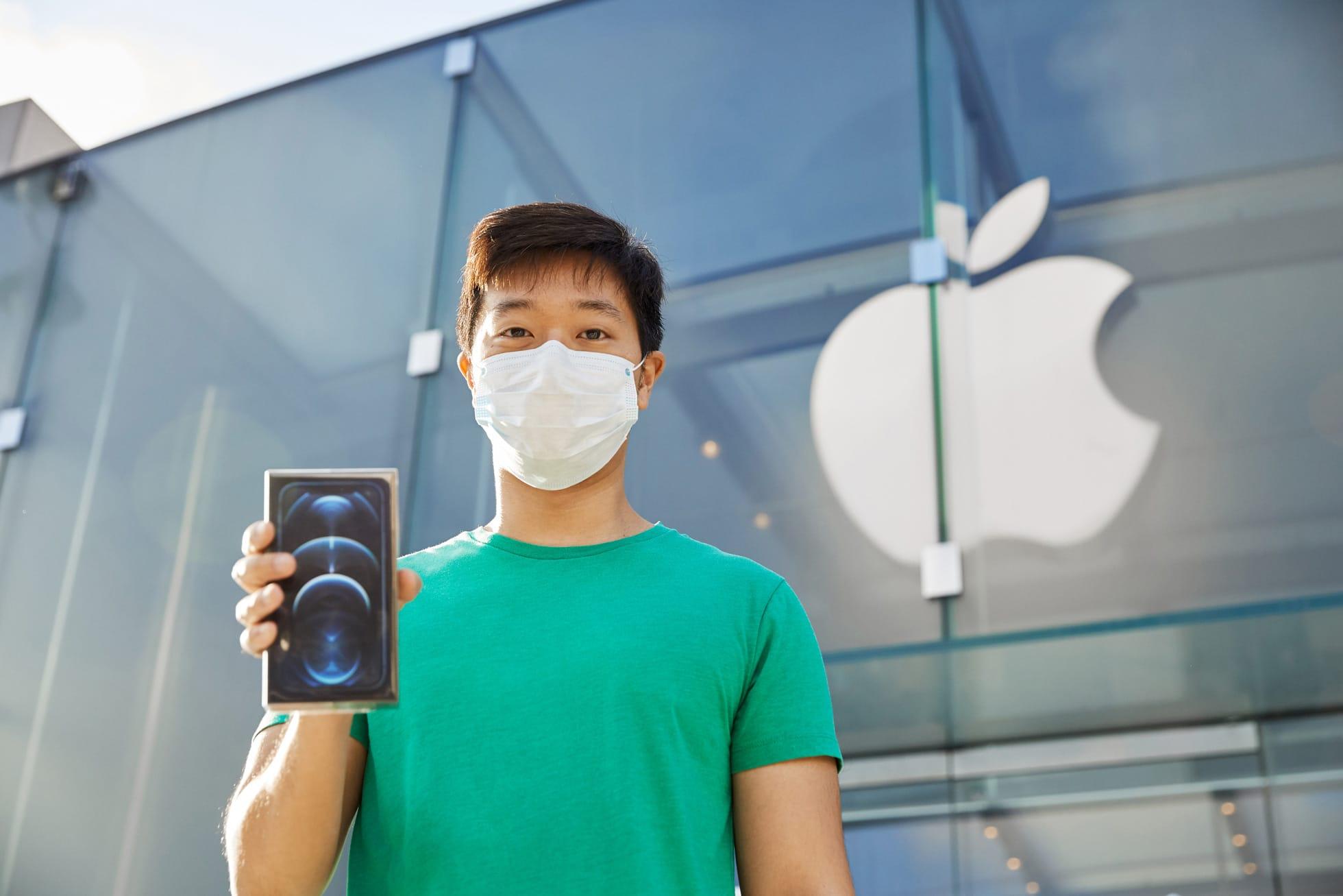 Consumidor saindo de loja da Apple com iPhone 12 Pro em mãos