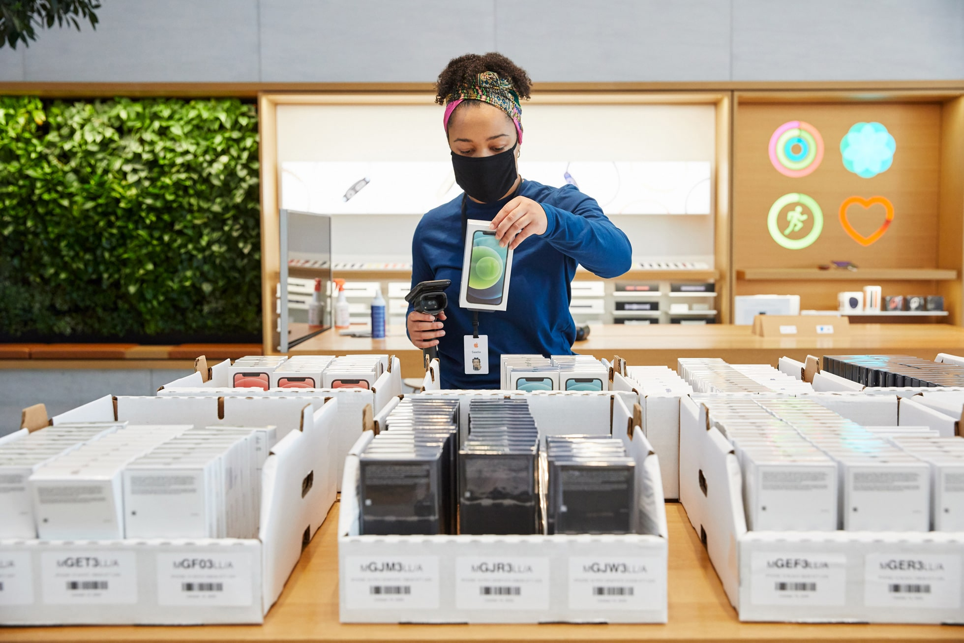 Empregada de Apple Store identificando caixas de iPhones 12 e 12 Pro