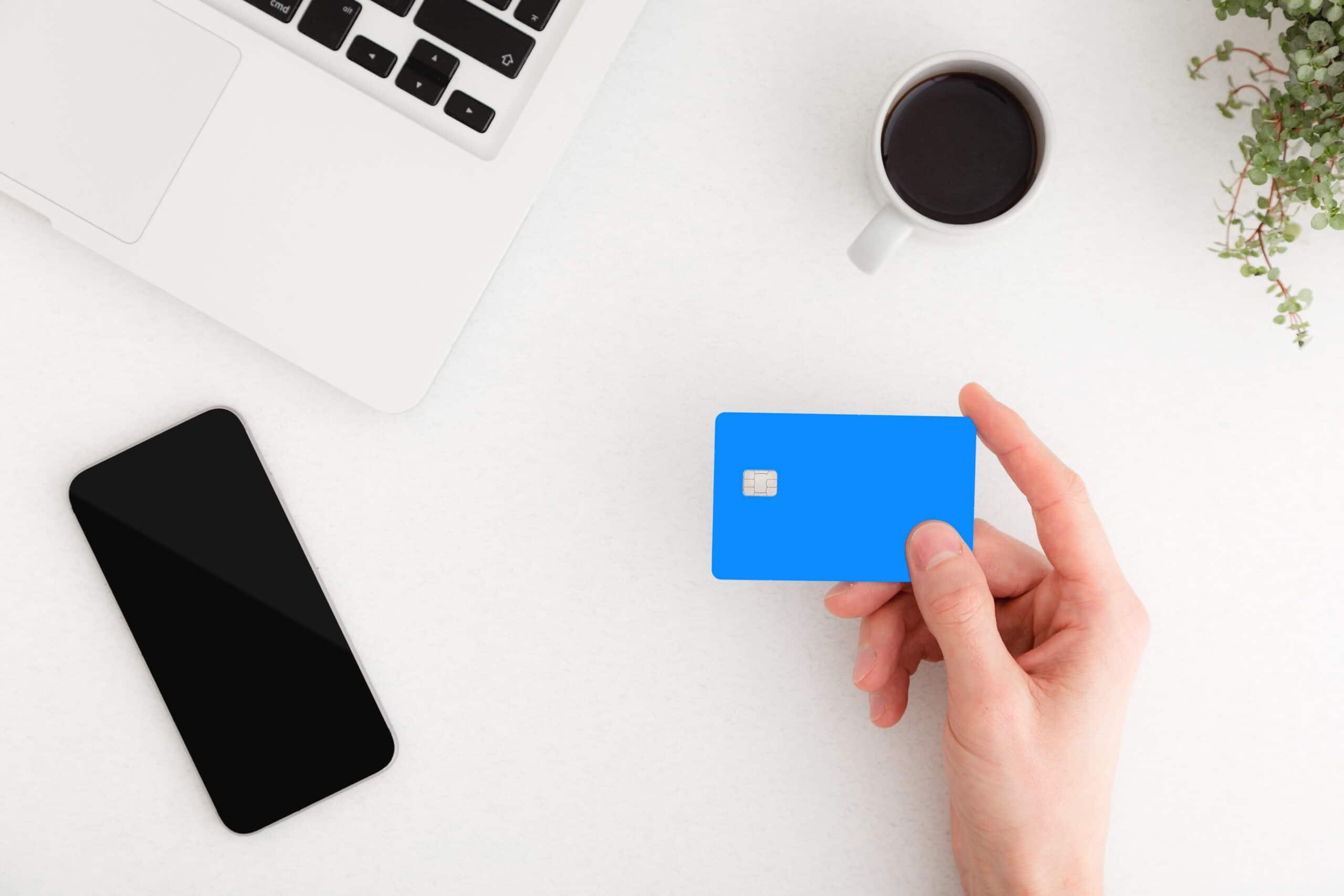 Pessoa segurando um cartão de crédito com um iPhone e um Mac
