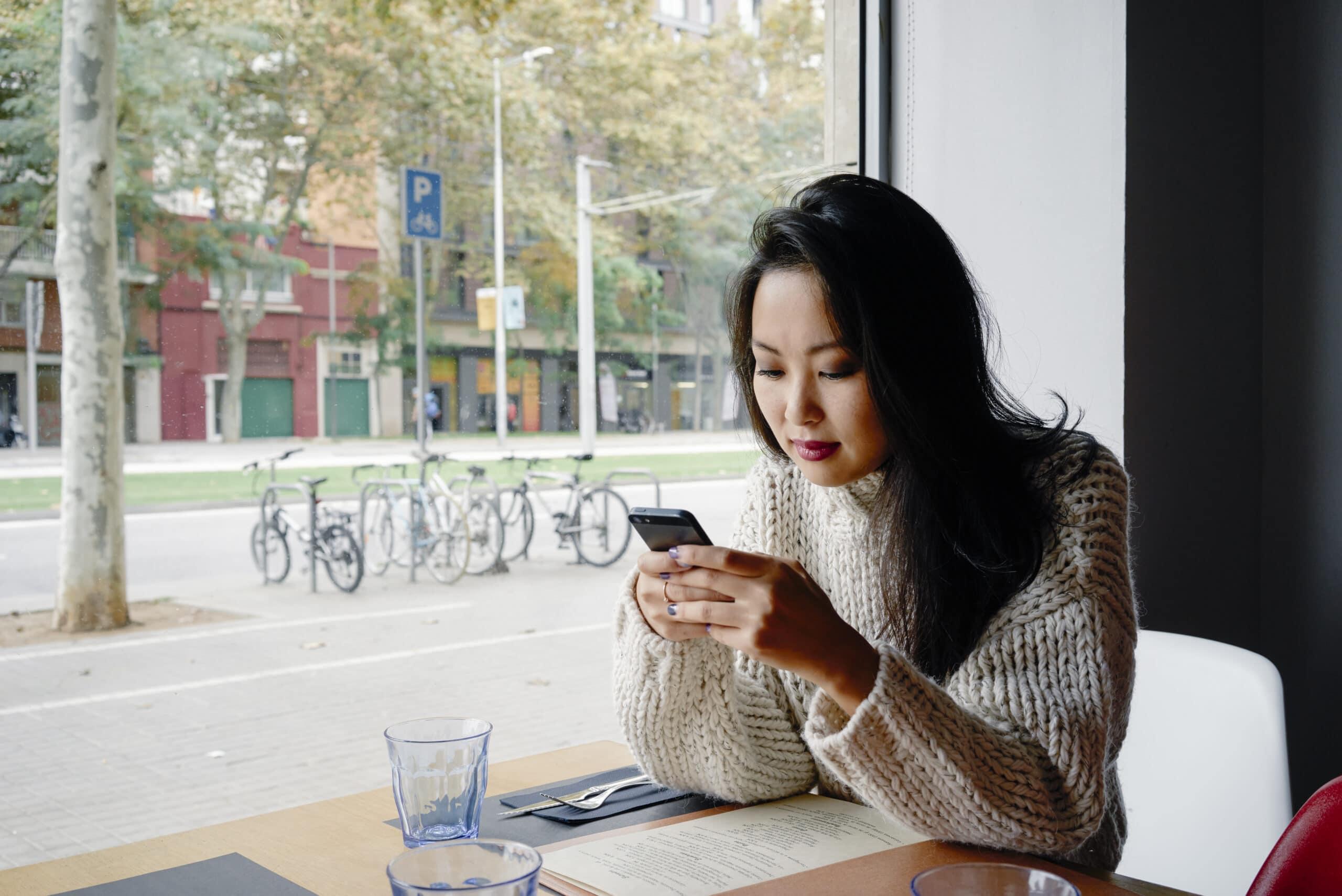 Mulher asiática mexendo em iPhone numa cafeteria