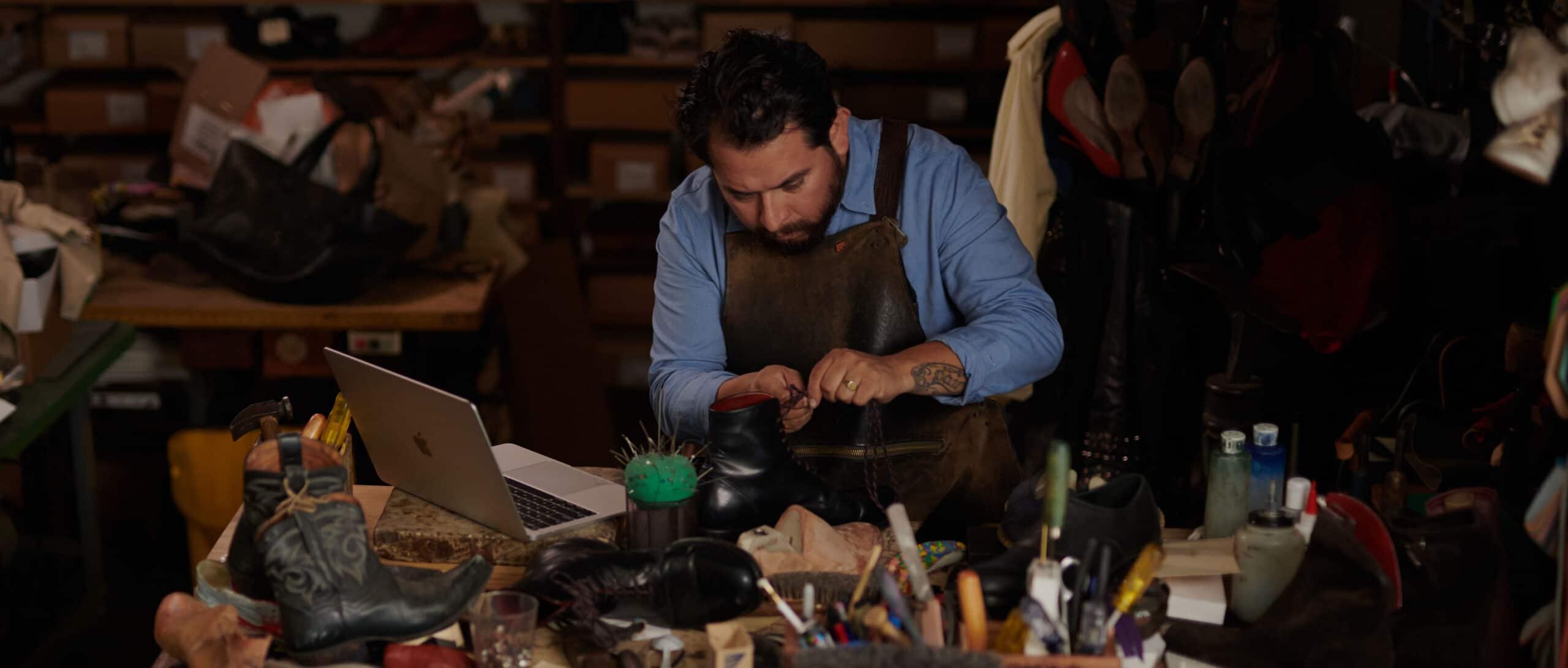 Sapateiro trabalhando com um Mac ao lado