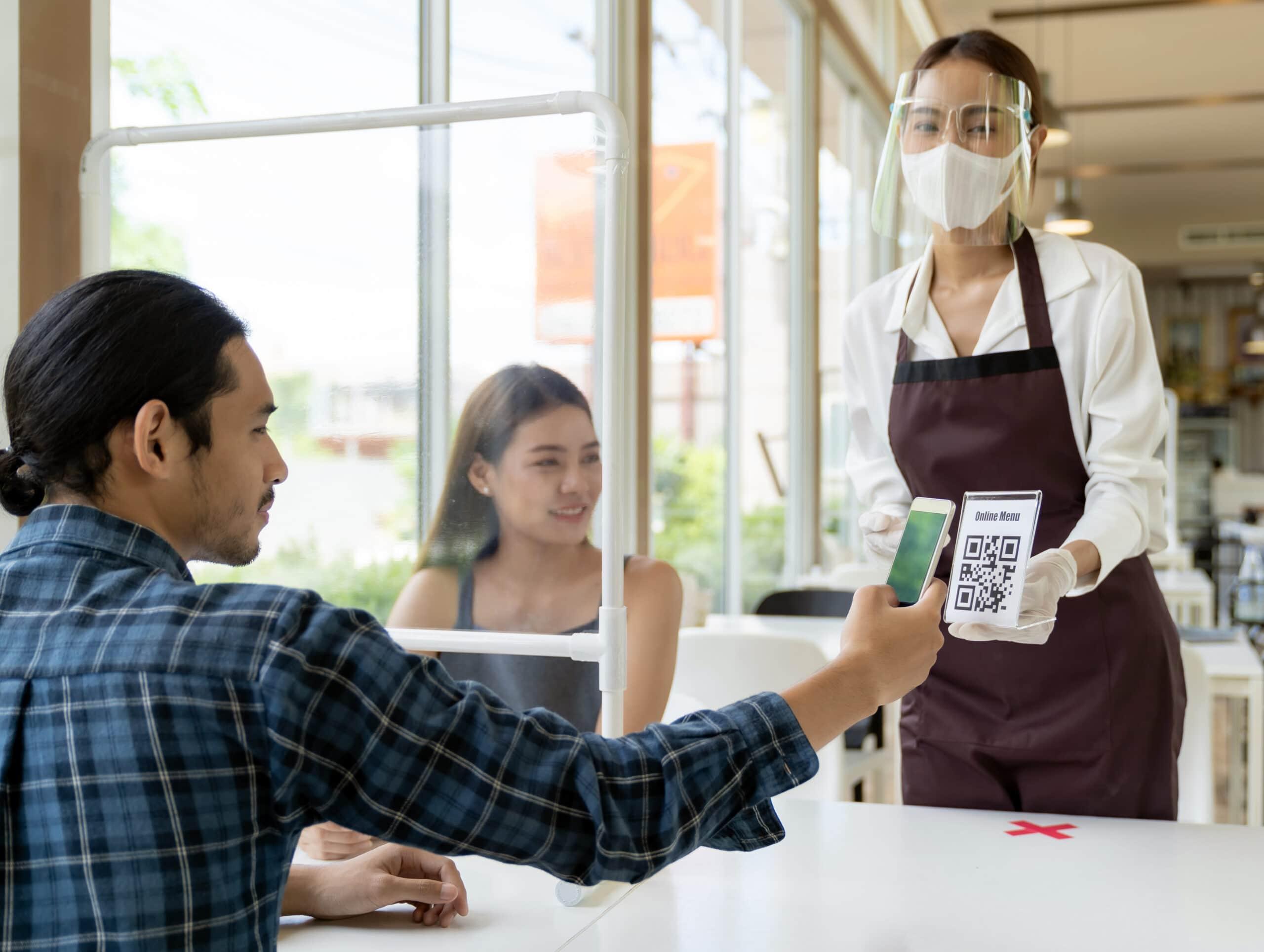 Pessoa escaneando um código QR dentro de um restaurante durante a pandemia do novo Coronavírus