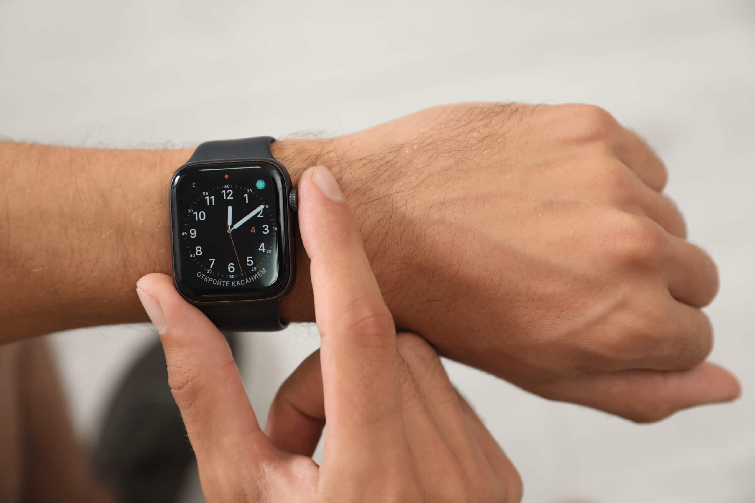 Homem mexendo em Apple Watch no pulso