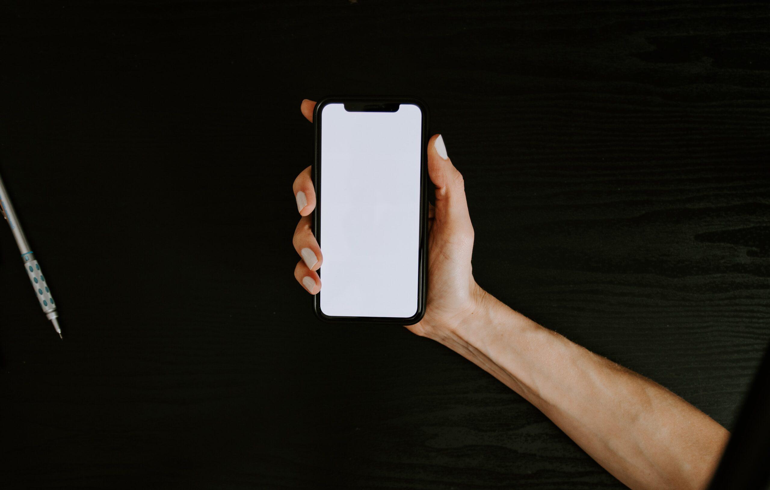 Mão segurando um iPhone com destaque para o notch