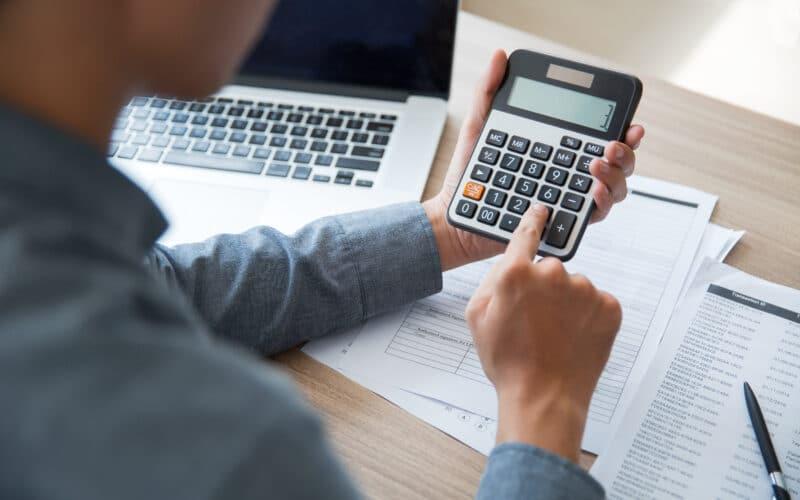 Pessoa usando uma calculadora com um Mac ao lado