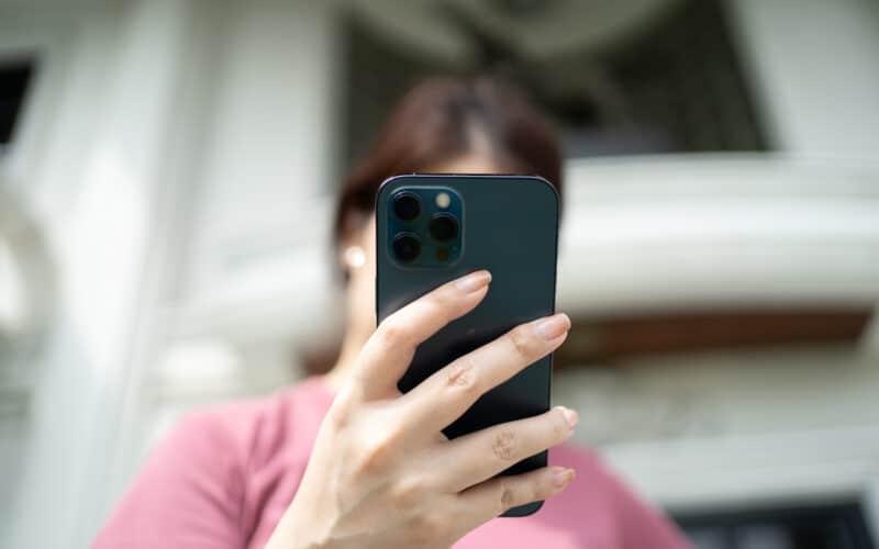 Mulher com iPhone 12 Pro Max na mão