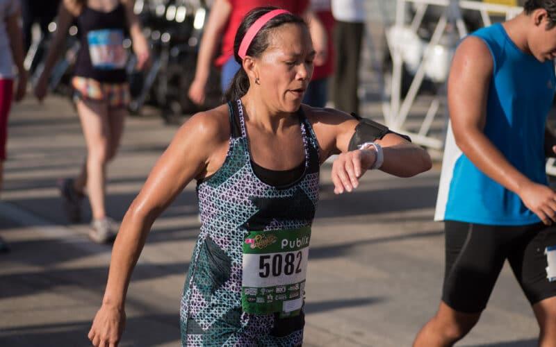 Corredora/maratonista olhando para o Apple Watch