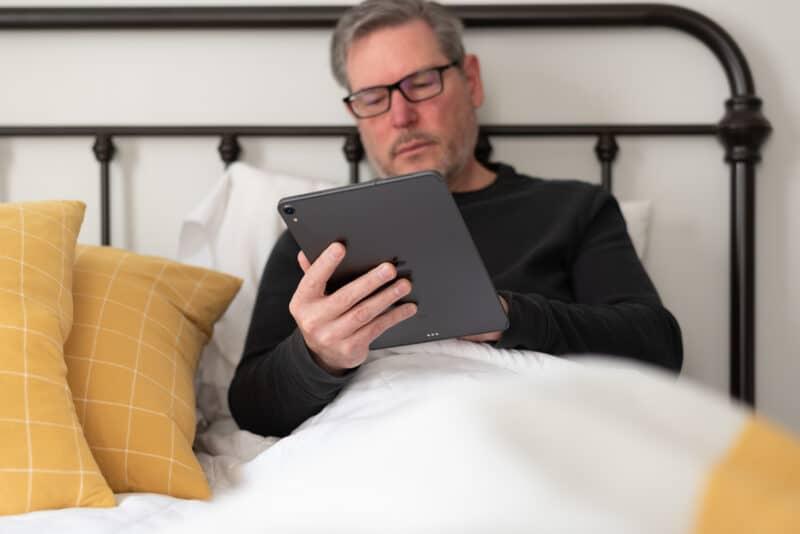 Homem trabalhando em iPad Pro na cama