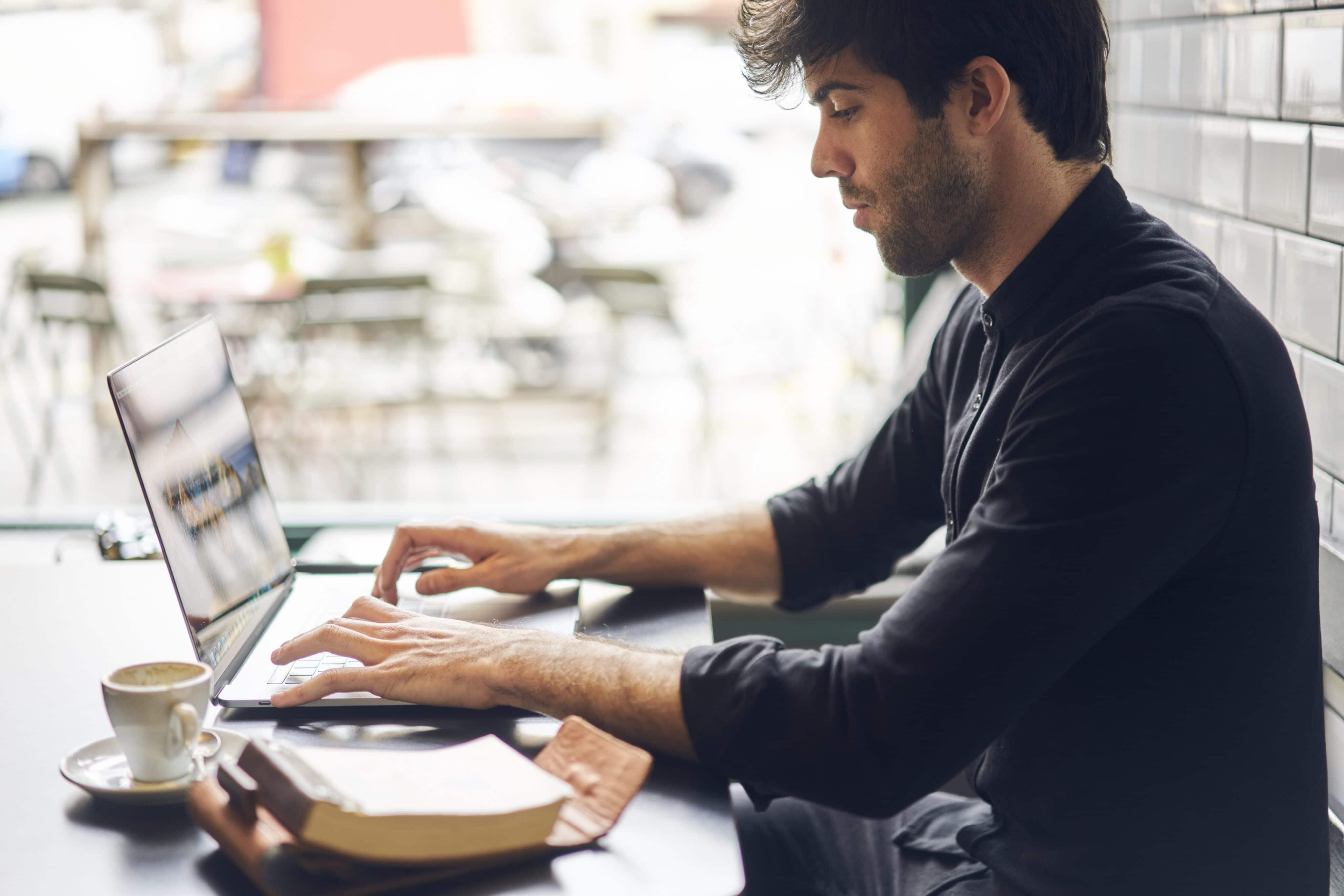 Homem trabalhando em MacBook Pro numa cafeteria