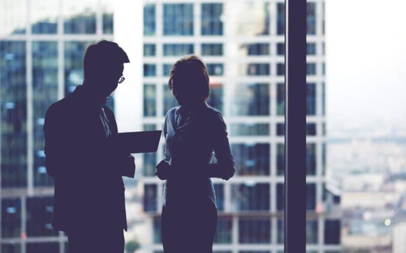 Homem e mulher trabalhando em iPad com prédios ao fundo
