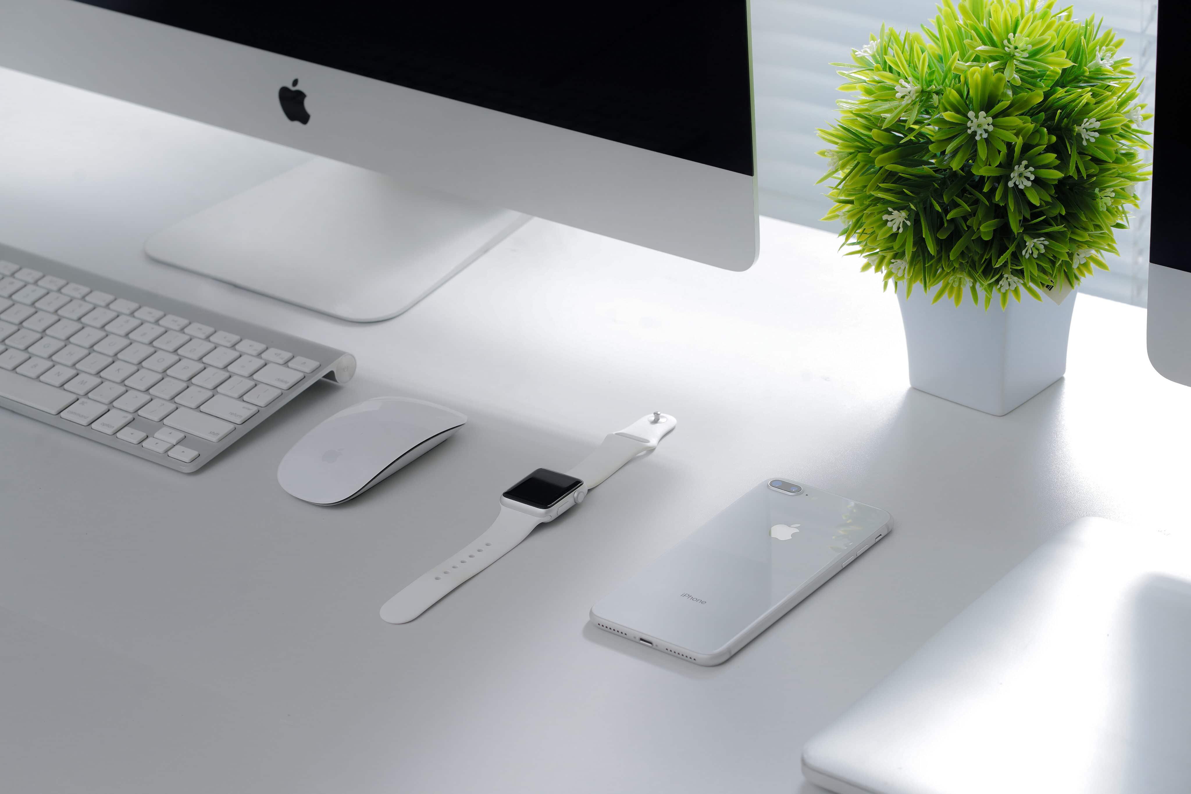 iMac, Magic Mouse, Apple Watch, iPhone 8 e MacBook Air numa mesa branca