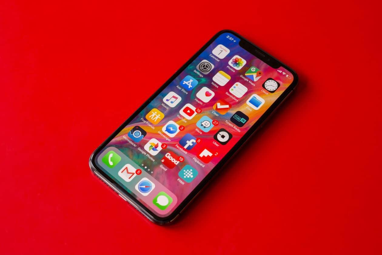 Tela de início de um iPhone com apps sobre mesa vermelha