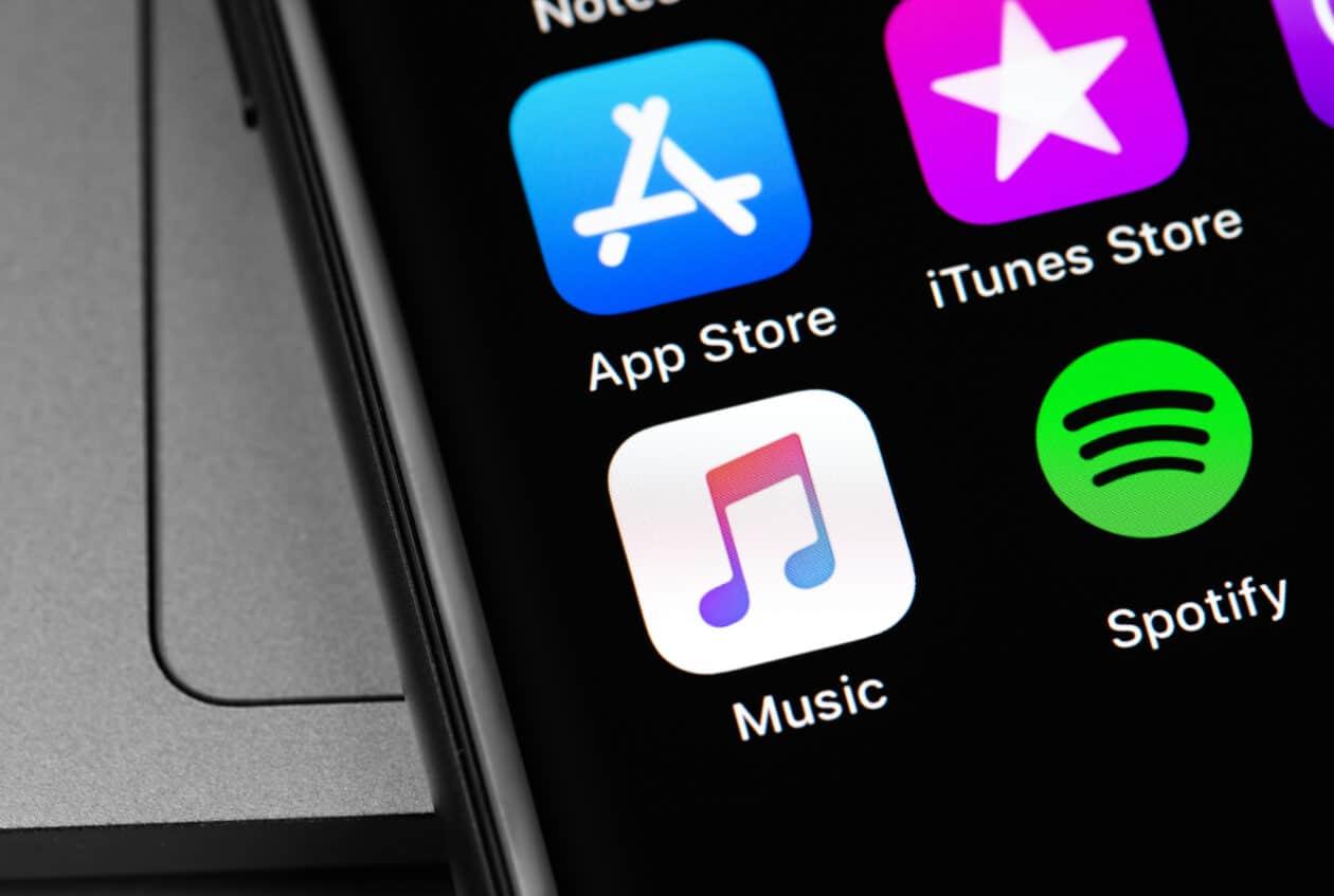 iPhone com ícones da App Store, da iTunes Store, do Música e do Spotify