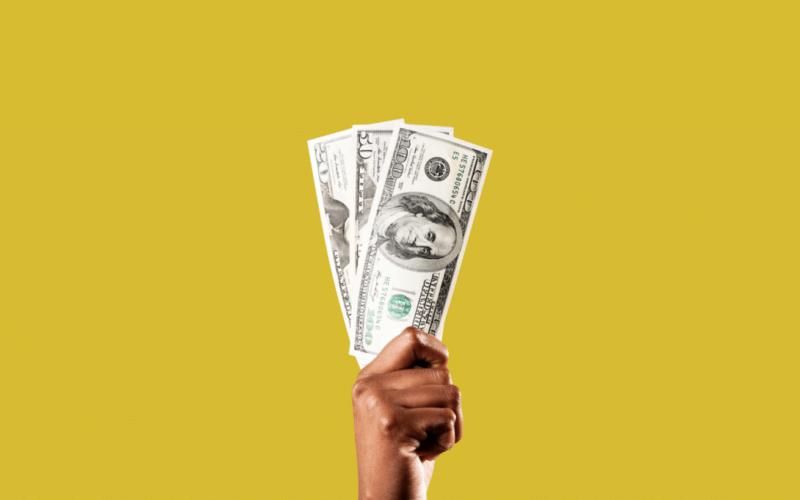 Mão segurando notas de dólares
