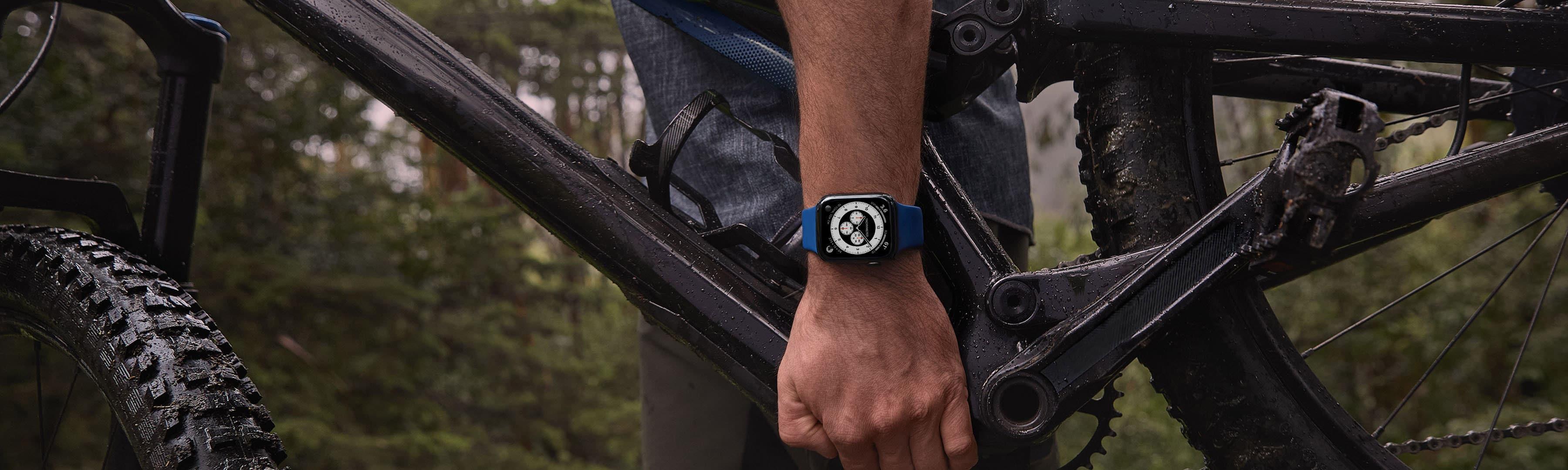 Homem segurando uma bicicleta com o Apple Watch no pulso
