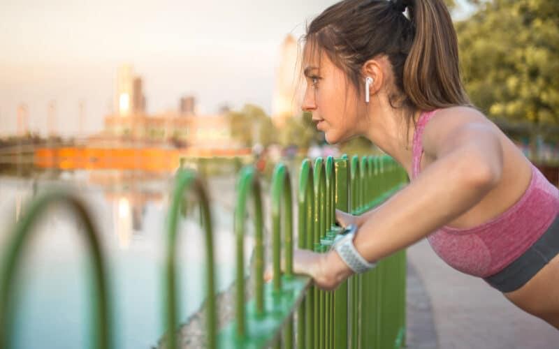 Mulher fazendo exercícios com AirPods e Apple Watch