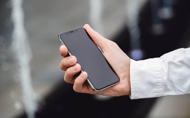 Homem segurando um iPhone