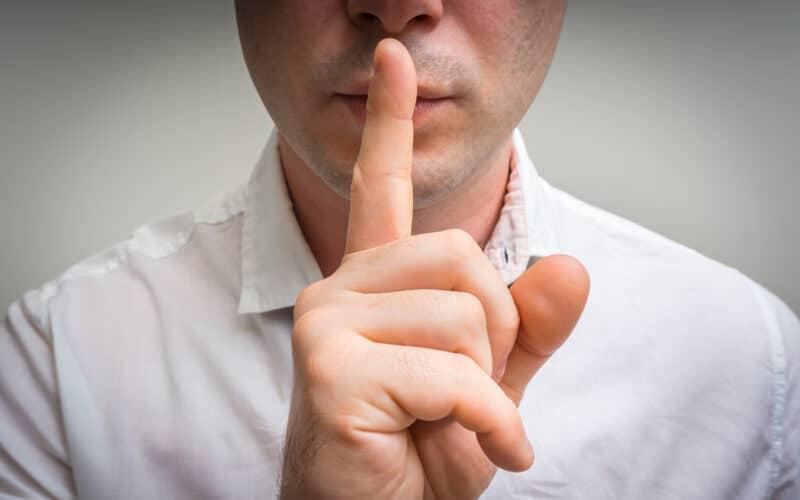 Homem colocando dedo na boca pedindo silêncio