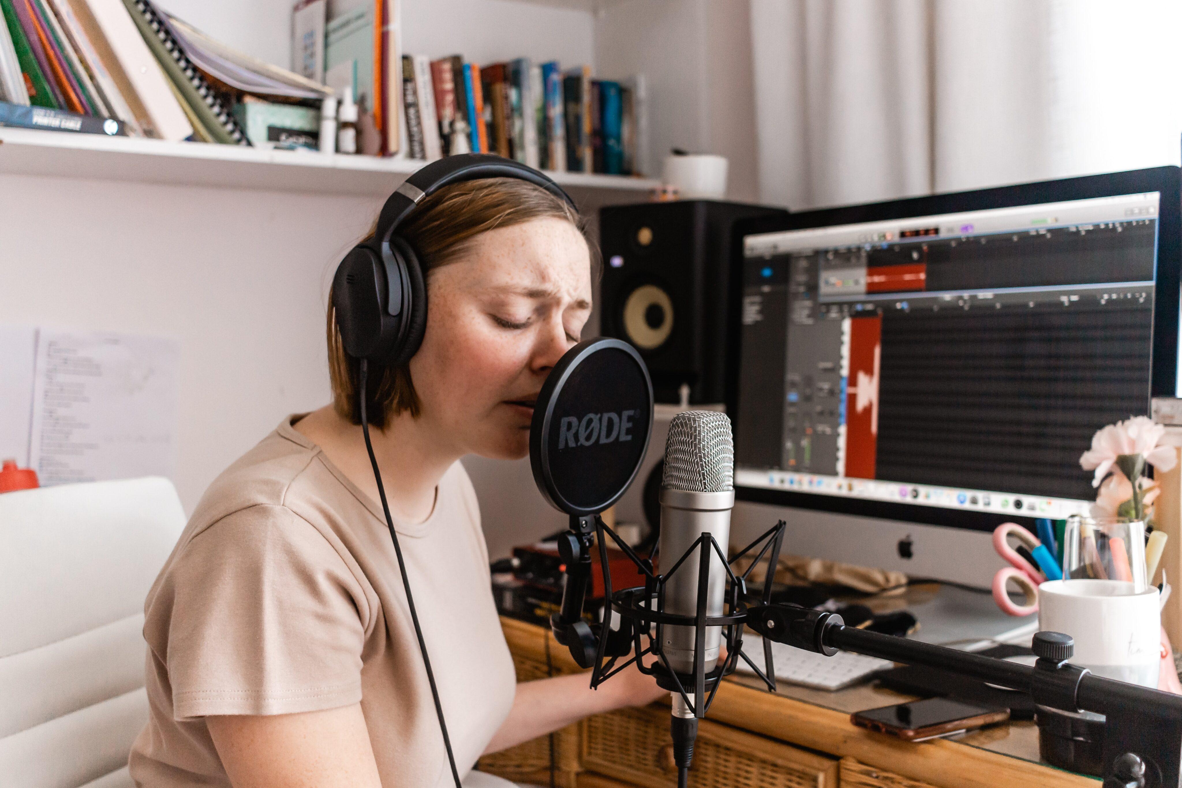 Mulher usando um iMac, um microfone e fones