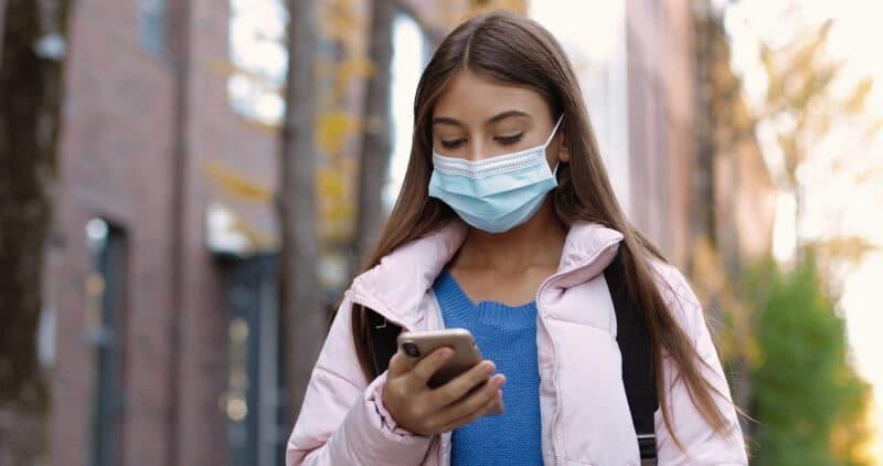 Garota de máscara usando iPhone