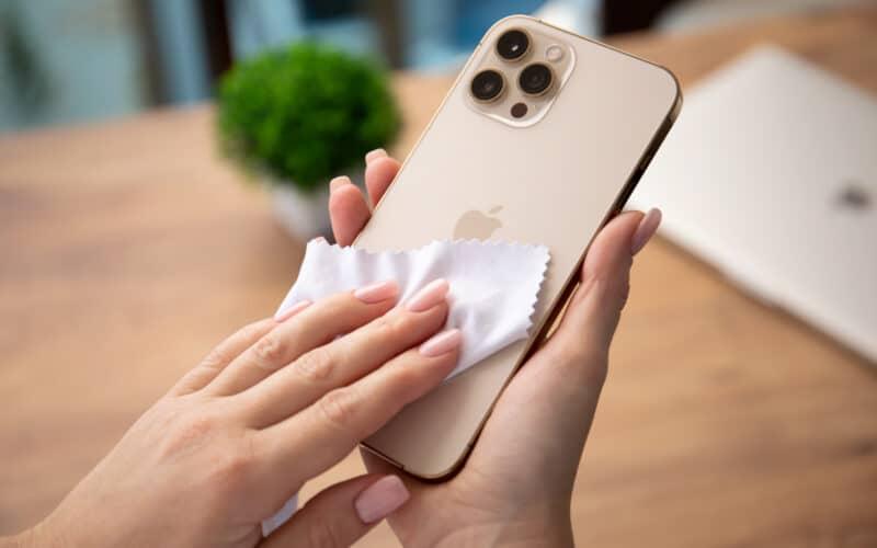 iPhone 12 Pro Max dourado sendo limpo com paninho de microfibra