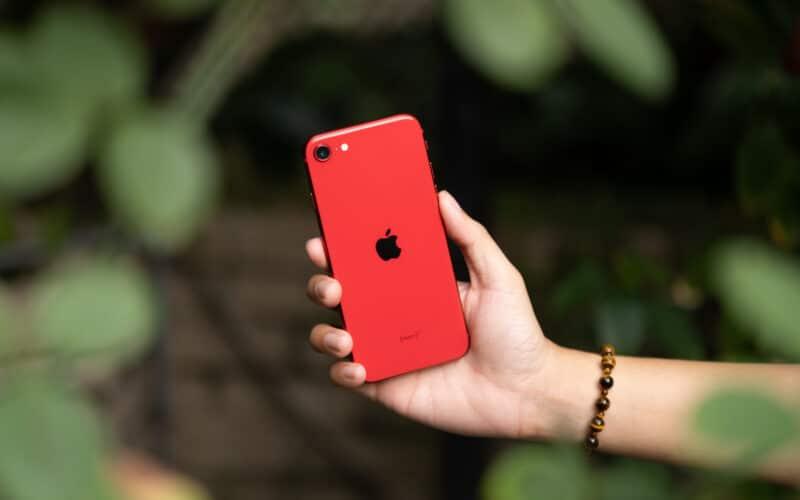 iPhone SE vermelho em mão