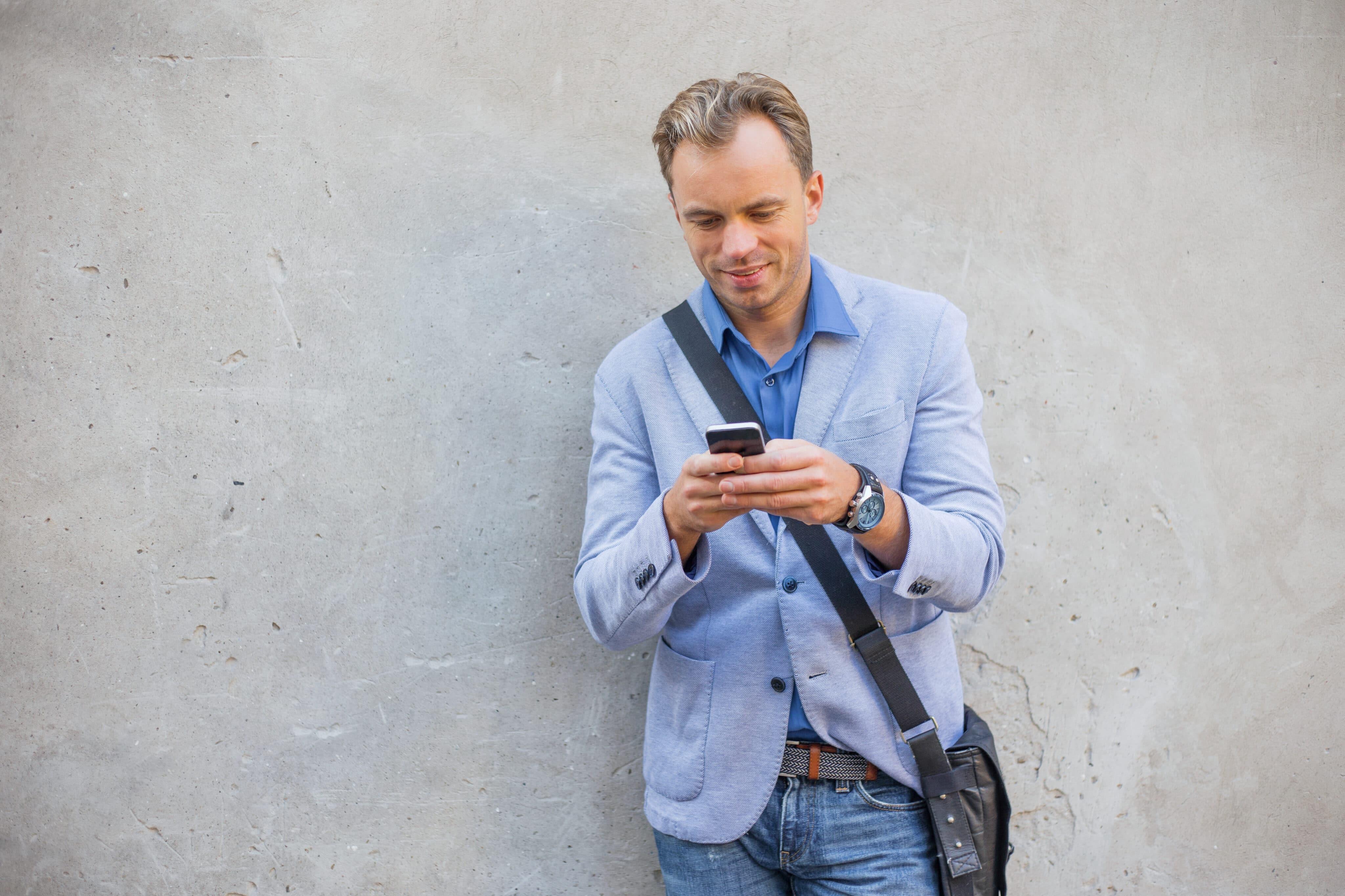 Homem em frente a parede usando iPhone
