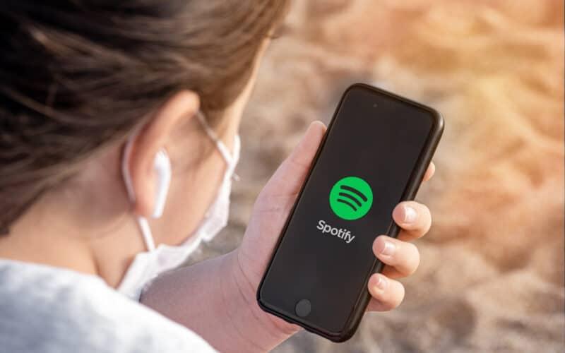Garota segurando iPhone com o app Spotify