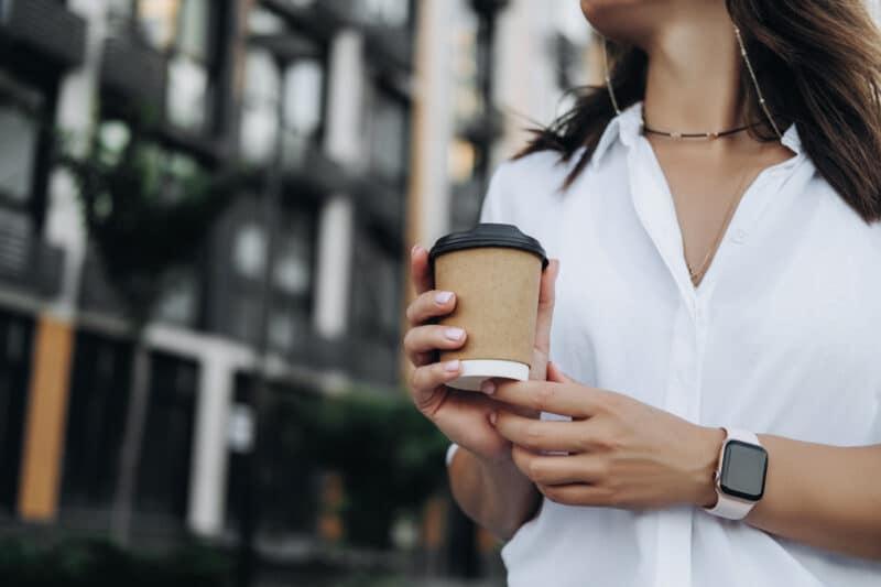Mulher com Apple Watch segurando um café