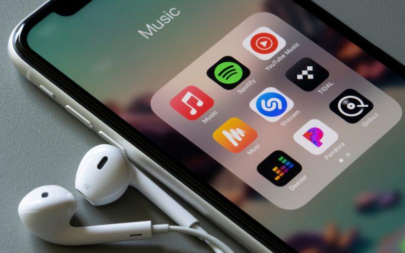 iPhone com EarPods e vários apps de música: Apple Music, Spotify, YouTube Music, Shazam, TIDAL, Deezer, Pandora e mais