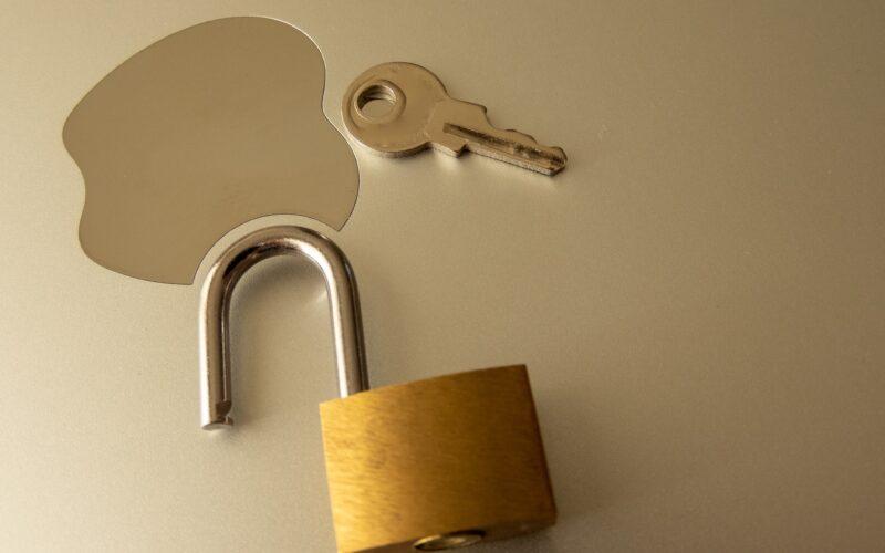 Logo da Apple ao lado de uma chave e de um cadeado aberto