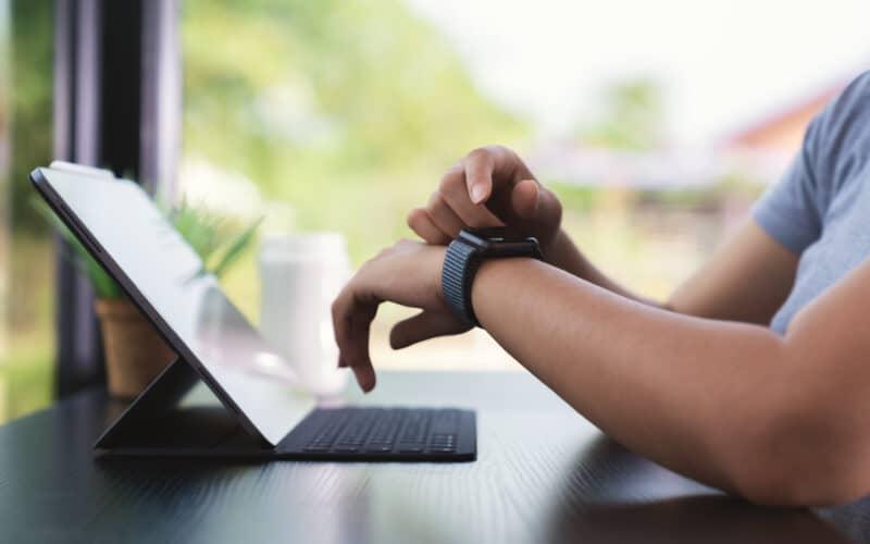 Homem usando um Apple Watch e um iPad