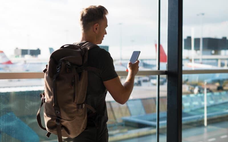 Homem viajando com um iPhone na mão