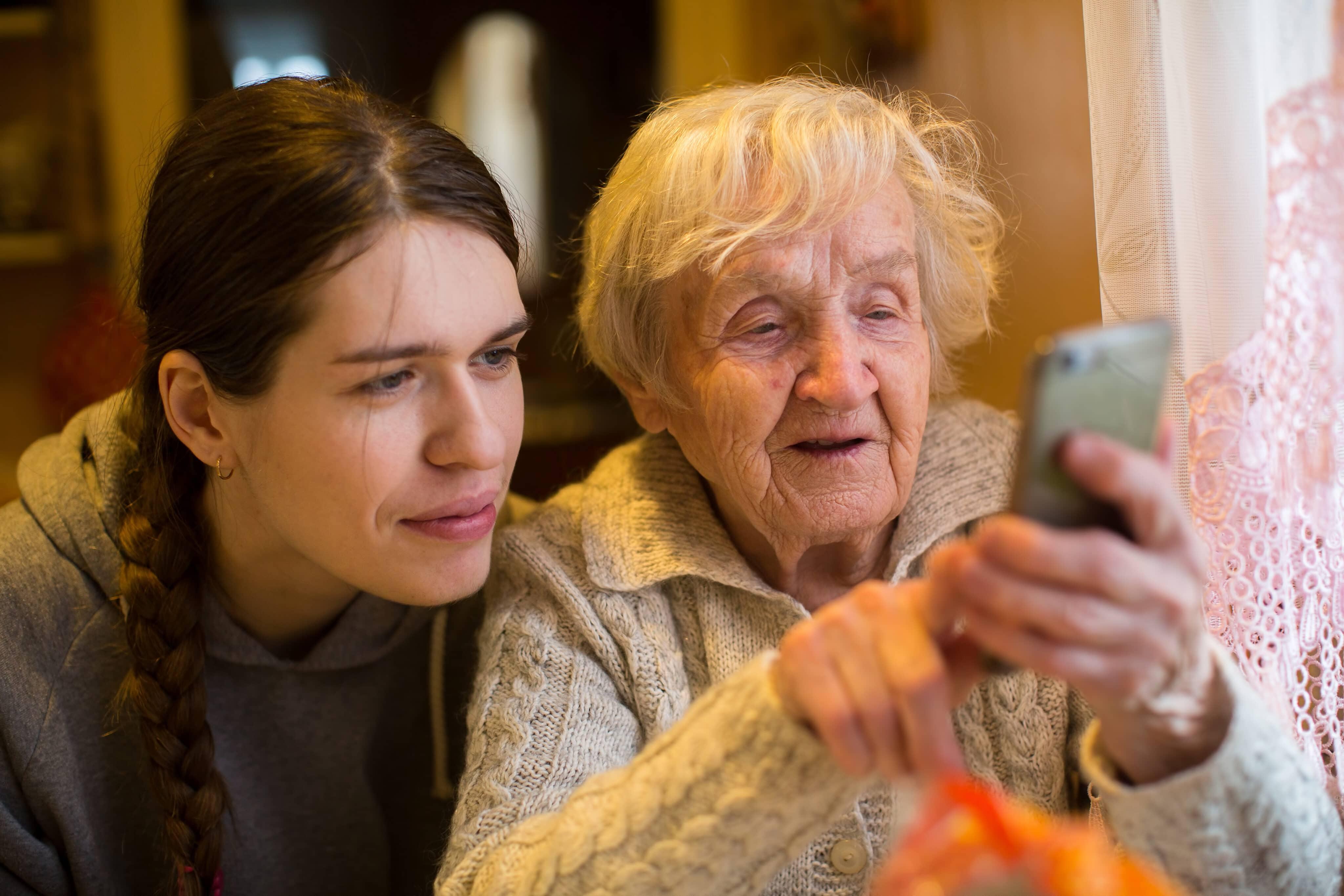Mulher mais velha segurando um smartphone com uma mais nova ao lado