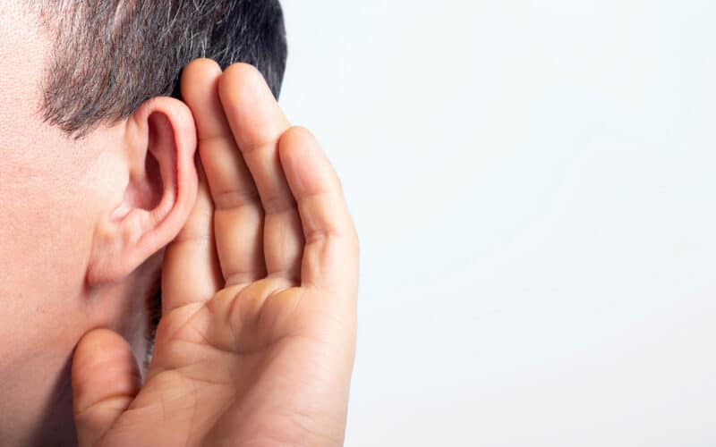 Homem fazendo uma concha com a mão para escutar melhor