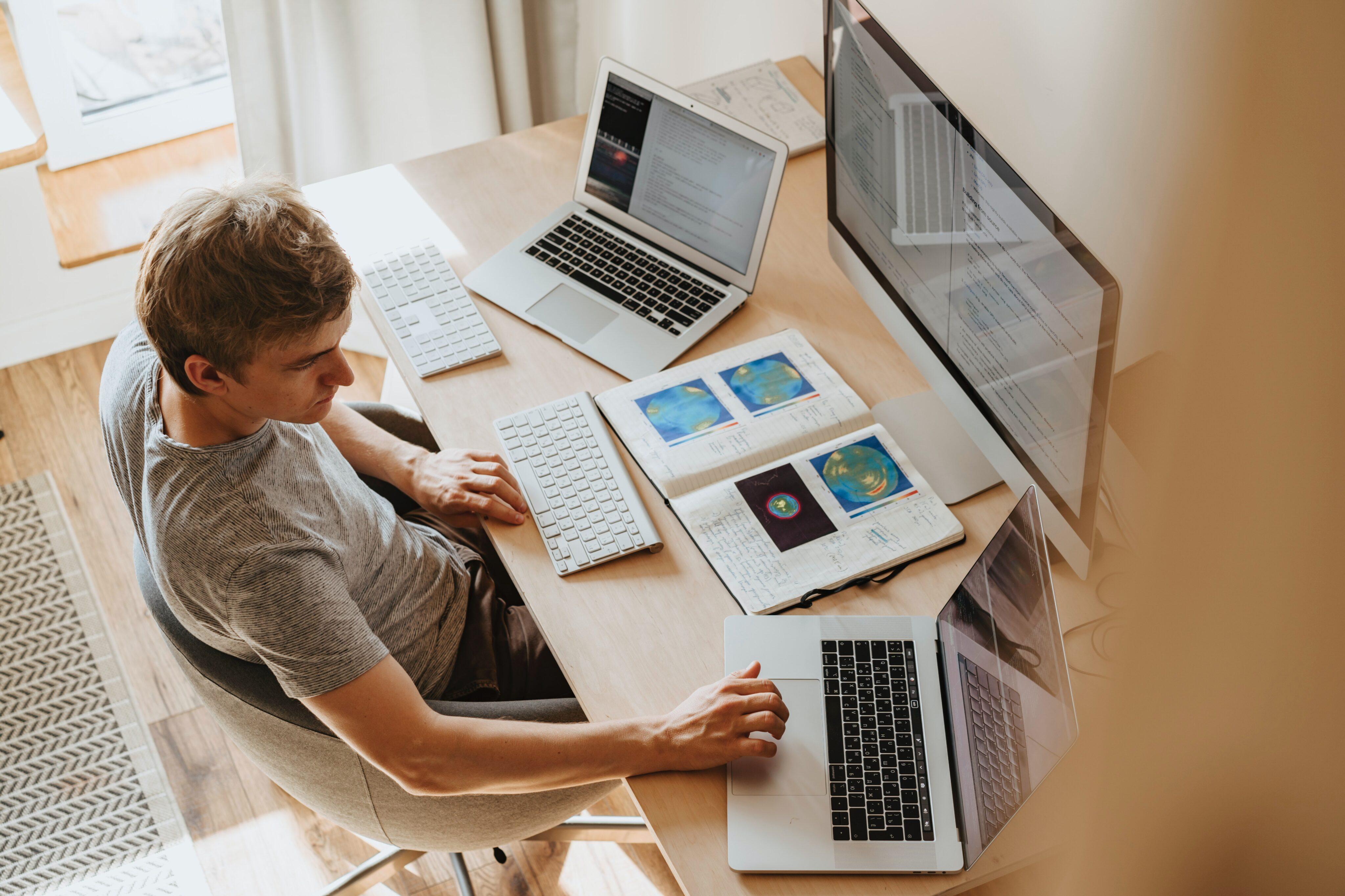 Homem trabalhando com vários Macs