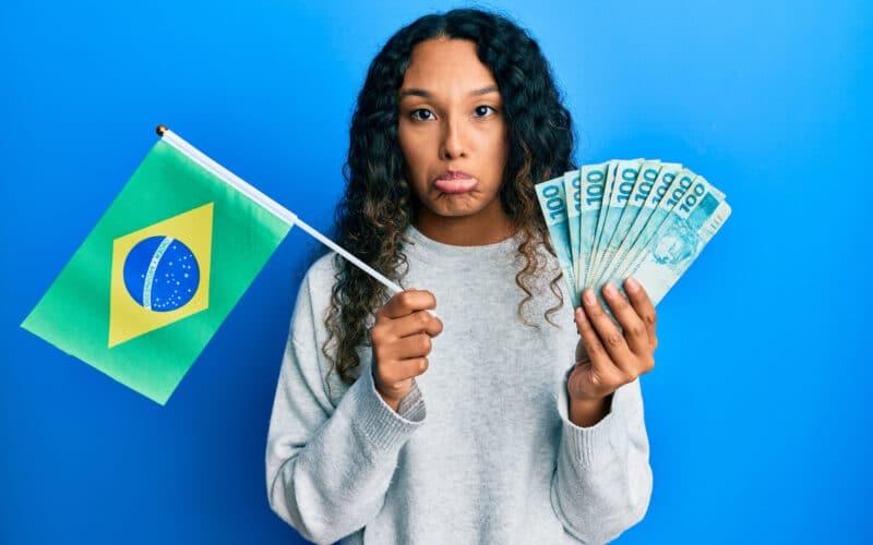 Mulher triste segurando uma bandeira do Brasil e dinheiro